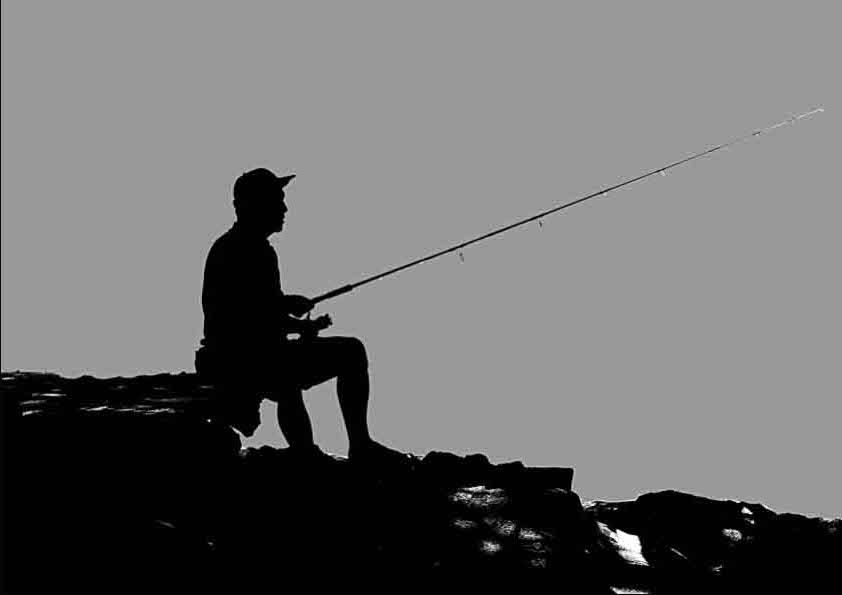 Pescador practicando spinning en rocas